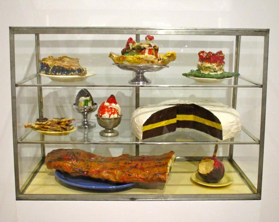 """Клас Олденбърг, """"Витрина със сладкиши 1"""". Зебло и муселин, напоени с гипс, оцветени с емайл във витрина от стъкло и метал. Ню Йорк, Музей за модерно изкуство, колекция """"Сидни и Хариет Джанис"""""""